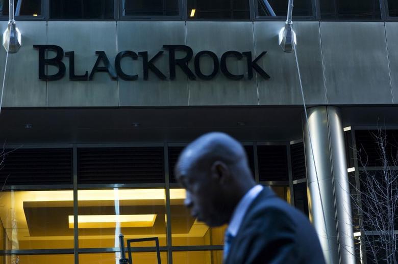 A man walks next to a BlackRock sign pictured in the Manhattan borough of New York, October 11, 2015.  REUTERS/Eduardo Munoz