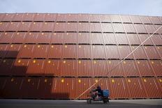 Foto de archivo de un hombre en moto pasando junto a contenedores apilados en un puerto en Shanghái, China. 17 de febrero de 2016. El desempeño comercial de China fue mucho peor que lo que esperado por los economistas en febrero, cuando las exportaciones cayeron un 25,4 por ciento respecto al mismo mes del año previo y las importaciones bajaron un 13,8 por ciento en términos denominados en dólares, mostraron datos el martes. REUTERS/Aly Song/Files