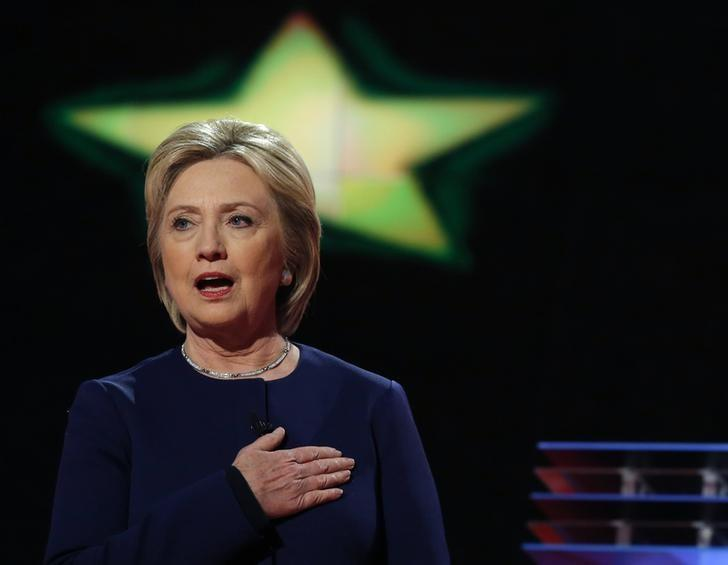 Democratic U.S. presidential candidate Hillary Clinton sings the U.S. National Anthem at the start of the Democratic U.S. presidential candidates' debate in Flint, Michigan, March 6, 2016.  REUTERS/Carlos Barria