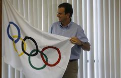 Prefeito do Rio de Janeiro, Eduardo Paes, posa com bandeira olímpica após entrevista no Rio. 04/08/2015 REUTERS/Ricardo Moraes