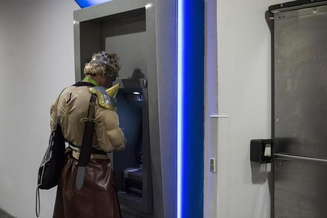 A man dressed as a character from Clash of Clans mobile game uses at an ATM at the New York Comic Con in Manhattan, New York, October 8, 2015.  REUTERS/Andrew Kelly