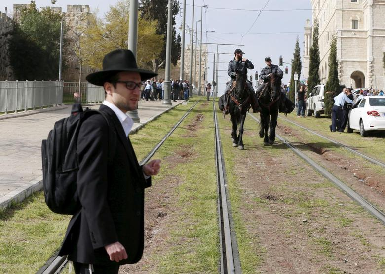 An ultra-Orthodox Jewish onlooker stands near Israeli mounted police near the scene where Israeli police said two Palestinian assailants carried out a drive-by shooting on a commuter bus before being shot dead by police opposite the Notre Dame Center just outside Jerusalem's Old City March 9, 2016. REUTERS/Ammar Awad