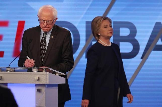 3月9日、米民主党の大統領候補指名争いは、8日に行われたミシガン州の予備選でヒラリー・クリントン前国務長官がバーニー・サンダース上院議員に予想外の敗北を喫する事態が起きた。写真はクリントン氏(右)とサンダース上院議員。フロリダ州で撮影(2016年 ロイター/Carlo Allegri)