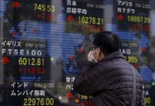 Un peatón mira un panel electrónico que muestra información bursátil, afuera de una correduría en Tokio, Japón, 26 de febrero de 2016. Las bolsas de Asia subían el jueves, apoyadas por un rebote en los precios del crudo y por las expectativas de que el Banco Central Europeo relajará su política monetaria más tarde en el día, emulando a las autoridades en otros lugares que buscan reforzar sus economías. REUTERS/Yuya Shino