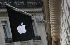 Флаг с логотипом Apple у входа в магазин Apple Store в Париже. 3 марта 2016 года. Apple Inc в четверг разослала приглашения журналистам на мероприятие 21 марта в штаб-квартире компании в Купертино, на котором могут быть представлены новые устройства. REUTERS/Christian Hartmann