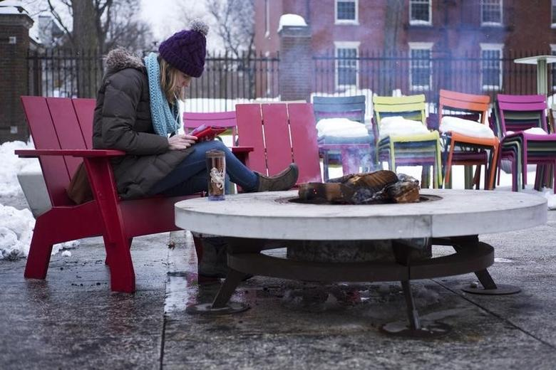 A woman reads a tablet beside a fire pit on cold winter evening outside the Science Center at Harvard University in Cambridge, Massachusetts February 18, 2015.     REUTERS/Brian Snyder