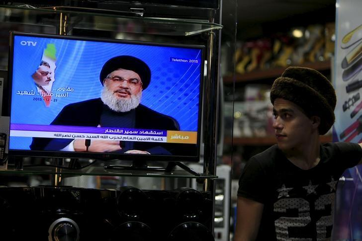 A youth watches Lebanon's Hezbollah leader Sayyed Hassan Nasrallah speaking on television inside an electronics shop in the port city of Sidon, southern Lebanon December 21, 2015.  REUTERS/Ali Hashisho