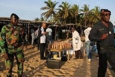 """Спасатели и  сотрудники службы безопасности на пляже Гран-Бассама после нападения боевиков. Шестнадцать человек, в том числе четверо европейцев, погибли в результате нападения боевиков североафриканского крыла """"аль-Каиды"""" на курортный город в Кот-д'Ивуаре в воскресенье. REUTERS/Joe Penney"""