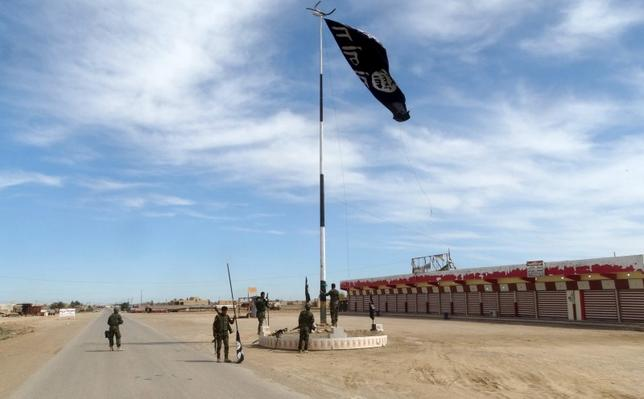 Iraqi security forces work on lowering the Islamic State flag, west of Ramadi, March 9, 2016. REUTERS/Stringer