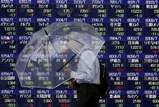 Мужчина с зонтом на фоне табло с котировками у биржи в Токио 8 сентября 2015 года. Японские фондовые индексы снизились по итогам торгов вторника, поскольку Банк Японии решил оставить монетарную политику без изменений, что привело к укреплению иены и падению котировок экспортных компаний. REUTERS/Issei Kato