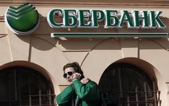 Мужчина проходит мимо отделения Сбербанка в Санкт-Петербурге 27 марта 2014 года. Крупнейший госбанк РФ Сбербанк увеличил в четвертом квартале 2015 года чистую прибыль, рассчитанную по международным стандартам, на 48 процентов до 72,6 миллиарда рублей в годовом выражении, сообщил банк во вторник. REUTERS/Alexander Demianchuk