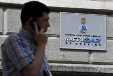 Мужчина говорит по мобильному телефону у офиса Нафтогаза в Киеве 1 июля 2015 года. Общая сумма требований российского Газпрома к украинской компании Нафтогаз в Стокгольмском арбитраже достигла $31,759 миллиарда, сообщил Газпром во вторник. REUTERS/Valentyn Ogirenko