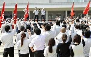 Members of the workers' union of Toyota Motor Corp. raise their fists as they shout slogans during a rally for the annual ''shunto'' wage negotiations at the company headquarters in Toyota, central Japan, in this photo taken by Kyodo March 8, 2016. Mandatory credit REUTERS/Kyodo