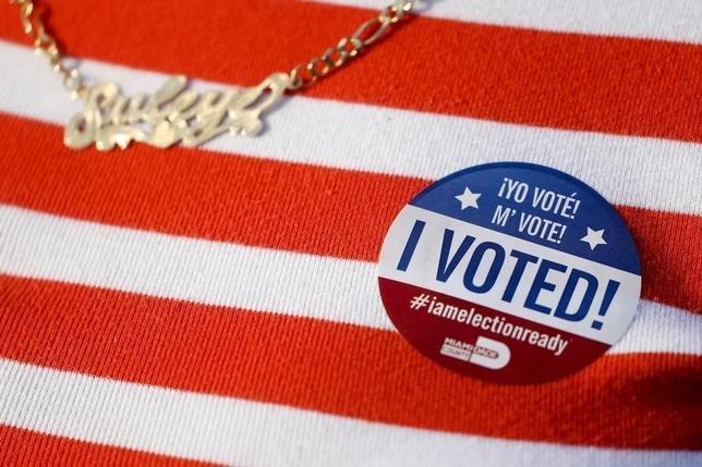 3月15日、米民主・共和両党大統領予備選は5州で投票が行われ、複数の地元メディアの報道によると、フロリダ州の共和党予備選は実業家ドナルド・トランプ氏が勝利の見通しとなった。選挙のシールを付けた女性、フロリダの投票所で撮影(2016年 ロイター/Carlo Allegri)