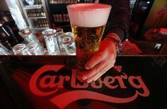 Бармен держит бокал пива Carlsberg в баре Санкт-Петербурга. Датская пивоваренная компания Carlsberg <CARLb.CO> останется в России несмотря на проблемы, с которыми она сталкивается, и обещает повысить доходность акционерного капитала в рамках стратегии, объявленной новым главой. REUTERS/Alexander Demianchuk