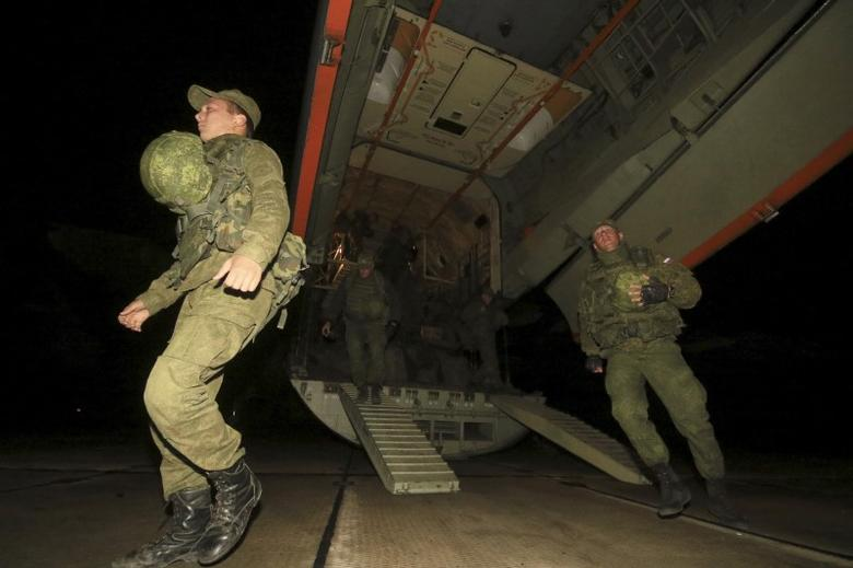 Russian marines, who guarded Russia's Hmeymim air base in Syria, disembark from a plane as they arrive at the Belbek military airport near the Black Sea port of Sevastopol, Crimea, December 28, 2015. REUTERS/Pavel Rebrov