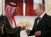"""Президент России Владимир Путина (справа) чокается с послом Саудовской Аравии Абдулрахманом аль-Расси на приеме в московском Кремле 28 мая 2015 года. Частичный вывод российских войск из Сирии - """"очень позитивный шаг"""", сказал министр иностранных дел Саудовской Аравии Адель аль-Джубейр в среду, выразив надежду, что это заставит президента Сирии Башара Асада пойти на уступки. REUTERS/Sergei Karpukhin"""
