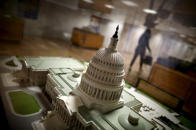 A woman walks by a miniature of the Capitol building at the Hart Senate Office Building at Capitol Hill in Washington, January 20, 2016.  REUTERS/Carlos Barria