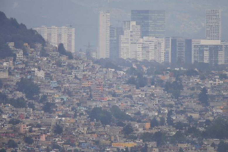 Buildings and houses stand shrouded in smog in Mexico City, March 16, 2016. Mexico City's government ordered traffic restrictions and recommended people stay indoors due to serious air pollution, issuing its second-highest alert warning for ozone levels for the first time in 13 years. REUTERS/Edgard Garrido