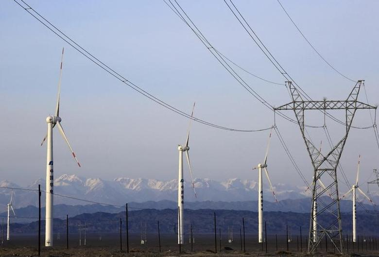 An electricity pylon is seen next to wind turbines at a wind power plant in Hami, Xinjiang Uighur Autonomous Region, China, March 21, 2015. REUTERS/Stringer