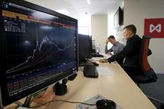 Трейдеры работают на московской бирже.  Осторожный тон заявлений главы ФРС США подстегнул спрос на рискованные активы в мире, и российские индексы на общей волне демонстрируют уверенный рост на торгах четверга.   REUTERS/Sergei Karpukhin