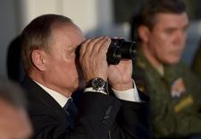 """Президент России Владимир Путин смотрит в бинокль, наблюдая за воинскими учениями на Донгузском полигоне под Оренбургом 12 сентябрря 2015 года. Путин предупредил в четверг, что за несколько часов способен вернуть прежнее число военных в Сирию, пообещал сбивать """"любые"""" угрожающие им цели в сирийском небе и назвал войну лучшим методом тренировки армии. REUTERS/Alexei Nikolsky/RIA Novosti/Pool"""