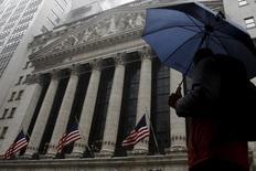 Человек идет мимо здания Нью-Йоркской фондовой биржи.  Уолл-стрит демонстрирует разнонаправленную динамику в четверг, на следующий день после того, как Федрезерв указал на меньшее, чем ожидалось ранее, количество повышений ставки в 2016 году, что позволило индексу S&P 500 закрыть торги среды на максимуме этого года.  REUTERS/Brendan McDermid
