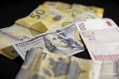 Купюры валют доллар США и манат в Тбилиси 15 января 2016 года. Азербайджан ограничил вывоз иностранной валюты резидентами и нерезидентами страны суммой в $10.000 с 16 марта, говорится в приказе председателя Центробанка Эльмана Рустамова, размещенного на сайте ЦБА. REUTERS/David Mdzinarishvili