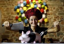 "Italian chef Cristina Palanti poses with a meat cleaver and cooking fork hovering over a plastic pig figurine at the ""L'e'Maiala"" restaurant in Florence in this October 6, 2012 file photo.    REUTERS/Alessandro Bianchi/files"