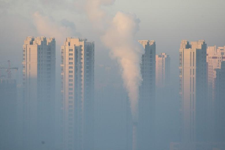 A chimney is seen in front of residential buildings during a polluted day in Harbin, Heilongjiang Province, China, January 21, 2016. REUTERS/Stringer