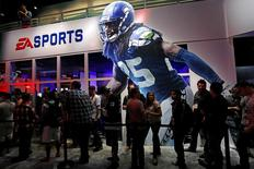 "People wait in-line under a ""Madden NFL 15"" billboard with an image of NFL player Richard Sherman at the Electronic Arts booth during the 2014 Electronic Entertainment Expo, known as E3, in Los Angeles, California June 11, 2014.  REUTERS/Jonathan Alcorn"