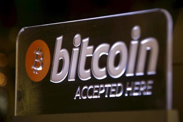 3月18日、仮想通貨のビットコインが小規模な投資家の間で支持を得ている。ビットコインに投資するために設計されたファンドが利用できるためだ。写真は店頭に飾られていたサイン。オーストラリア・シドニーで昨年9月撮影(2016年 ロイター/David Gray)