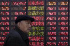 Un inversor camina junto a un tablero electrónico que muestra información bursátil, en una correduría en Shanghái, China, 14 de marzo de 2016. Las acciones chinas cerraron a la baja el martes, arrastradas por una ola de ventas de papeles en el sector financiero. REUTERS/Aly Song