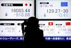 Женщина говорит по телефону на фоне табло с котировками у биржи в Токио 9 февраля 2016 года. Японские акции закрыли волатильные торги среды в минусе, поскольку инвесторы пытались найти новые катализаторы, в то время как многие из них сохраняли осторожность на фоне колебаний пары доллар/иена. REUTERS/Yuya Shino