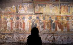 A visitor looks at frescoes inside the sixth-century Santa Maria Antiqua church in Rome, Italy, March 17, 2016. REUTERS/Max Rossi
