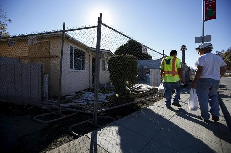Workers walk a past row of fenced off houses in East Palo Alto, California December 16, 2015.  REUTERS/Stephen Lam