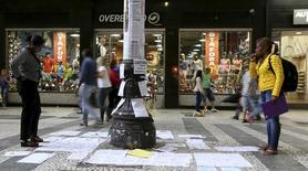 Unas personas observando anuncios de empleos pegados en un poste en Sao Paulo, Brasil, mar 19, 2015. La tasa nacional de desempleo de Brasil subió poco más de lo previsto a 9,5 por ciento en los tres meses hasta enero, dijo el jueves el estatal Instituto Brasileño de Geografía y Estadística (IBGE).  REUTERS/Paulo Whitaker