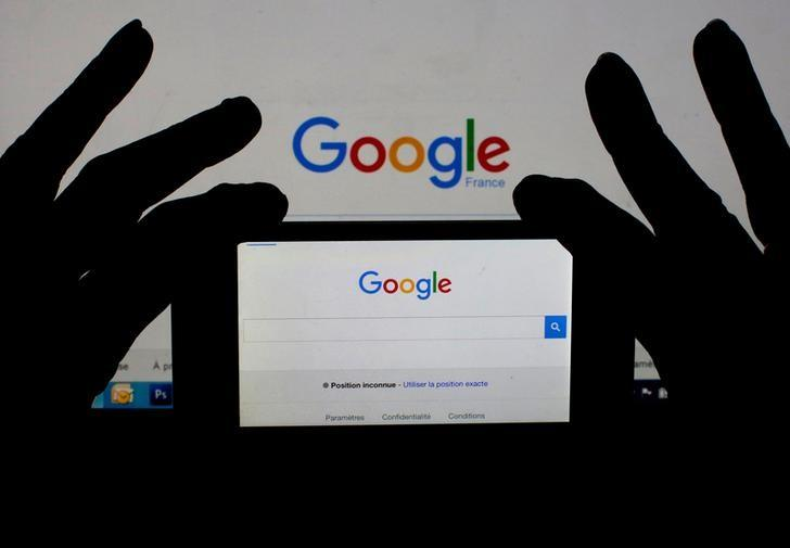A woman holds her smart phone which displays the Google home page, in this picture illustration taken February 24, 2016.  REUTERS/Eric Gaillard/Illustration