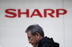 A pedestrian walks under a logo of Sharp Corp outside an electronics retail store in Tokyo, Japan, February 26, 2016.  REUTERS/Yuya Shino