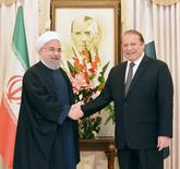 Pakistan's Prime Minister Nawaz Sharif (R) shakes hands with Iranian President Hassan Rouhani at the Prime Minister's house in Islamabad, Pakistan, in this March 25, 2016 handout photo. REUTERS/Press Information Department(PID)/Handout via Reuters