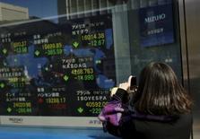 Una mujer toma fotografías de una pantalla que muestra varios índices de mercados. afuera de una correduría en Tokio, Japón. 10 de febrero de 2016. El dólar subía el lunes y la mayoría de los mercados de Asia cedía en momentos en que los inversores aguardan unos datos económicos estadounidenses y discursos de funcionarios de la Reserva Federal que podrían señalar más aumentos de las tasas de interés que lo previsto. REUTERS/Thomas Peter
