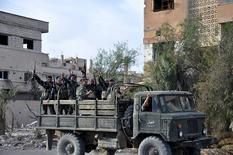 """Бойцы правительственных сил в кузове военного грузовика в Пальмире 27 марта 2016 года. Правительственная армия Сирии, поддерживаемая российскими воздушными ударами, в понедельник продолжает наступление на боевиков """"Исламского государства"""" после взятия Пальмиры. REUTERS/SANA/Handout via Reuters"""