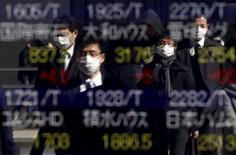 En la imagen, peatones se reflejan en un tablero electrónico que muestra los índices de mercado de varios países en una casa de valores de Tokio, el  26 de febrero de 2016. Las bolsas de Asia se debilitaban el martes y el dólar recuperaba parte del terreno perdido después de que datos económicos pesimistas en Estados Unidos contribuyeron a una sesión mediocre en Wall Street. REUTERS/Yuya Shino