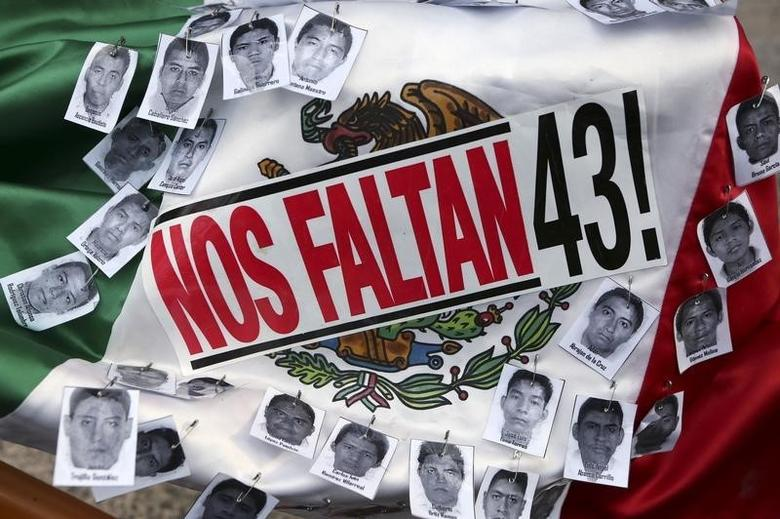 Pictures of the missing students of Ayotzinapa College Raul Isidro Burgos and a sticker that reads ''We are missing 43'', are seen over a Mexican flag during a march to mark the 16-month anniversary of their disappearance, in Mexico City, January 26, 2016. REUTERS/Ginnette Riquelme