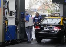 Un taxista llena el estaque de su vehículo en una gasolinería en Buenos Aires. 31 de julio de 2014. El Gobierno argentino aumentó el viernes la proporción de etanol que debe contener el combustible elaborado en base a gasolina, a un 12 por ciento desde un 10 por ciento, con el fin de dar un impulso a la golpeada industria azucarera local. REUTERS/Enrique Marcarian