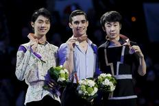 Figure Skating - ISU World Figure Skating Championships - Mens Free Skate Program - Boston, Massachusetts, United States - 01/04/16 - Silver medalist Yuzuru Hanyu (L) of Japan, gold medalist Javier Fernandez (C) of Spain, and bronze medalist Jin Boyang of China pose for photographs on the awards podium. - REUTERS/Brian Snyder