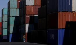 A worker walks in a container area at a port in Tokyo, Japan January 25, 2016. REUTERS/Toru Hanai