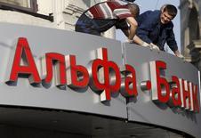 Рабочие устанавливают вывеску отделения Альфа-банка в Москве. 19 апреля 2013 года. Одна из крупнейших частных банковских групп РФ - Альфа-банк - в 2015 году увеличила чистую прибыль по международным стандартам отчетности в 15 раз до $480 миллионов, следует из сообщения банка. REUTERS/Sergei Karpukhin (RUSSIA - Tags: BUSINESS)