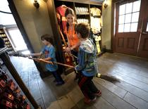 "Dove Rudman (C) and her children, Wyatt (L) and Cody try out witch brooms for sale inside Dervish and Banges general store in Hogsmeade Village during a soft opening and media tour of ""The Wizarding World of Harry Potter"" theme park at the Universal Studios Hollywood in Los Angeles, California in this picture taken March 22, 2016.  REUTERS/Kevork Djansezian"