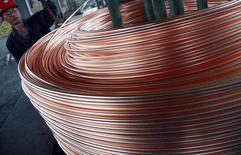 Imagen de archivo de un trabajador descargando un rollo de cobre en una fábrica en Nantong, China, jun 18, 2011. Los precios del cobre caían el miércoles presionados por un dólar más fuerte, mientras que los del aluminio tocaban mínimos de casi una semana en medio de la creciente preocupación por el reinicio de operaciones en fundiciones chinas, que se suma al temor por el exceso global de suministros. REUTERS/China Daily